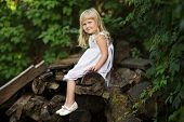 Little girl sitting on old boards
