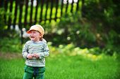 stock photo of crying boy  - little boy standing on lawn and crying - JPG