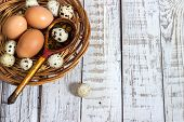chicken and quail eggs with a wooden spoon
