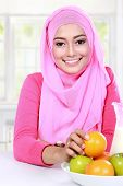 foto of muslimah  - portrait cheerful young muslim woman had a fruits for breakfast - JPG