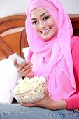 picture of muslimah  - portrait of young woman wearing hijab holding a mobilephone and a bowl of popcorn on bed - JPG