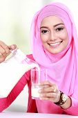 stock photo of muslimah  - close up portrait of young muslim woman pouring milk into a glass - JPG