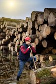 picture of ax  - Young lumberjack having break leaning against ax on trunk
