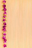 Frame Of Dried Pink Rose Flowers On Wooden Striped Background, Closeup