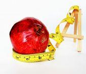 Weight Loss .Measuring tape wrapped around  tasteful fruit garnet
