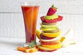Fresh spring juice and pile of slice fruits and vegetables