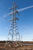 picture of electricity pylon  - High voltage electricity pylon with workers on it building up a new power line on blue sky background with clouds - JPG