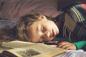 Toned portrait of cute school girl sleeping on the book