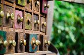 Постер, плакат: Antique Spice Drawers with Brass Handles with Blurred Green Foliage Background