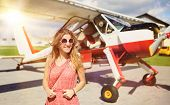 picture of aeroplane  - Beautiful woman in summer dress standing in front of small vintage aircraft - JPG