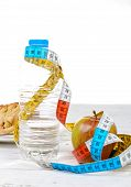 Bottle Of Water And  Apple With Meter Ribbon