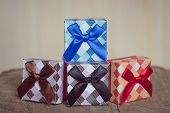 Gift box with blue bow on wood background