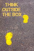 Yellow Footsteps On Sidewalk Towards Think Outside The Box Message