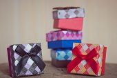 Gift box with red and black bow on wood background
