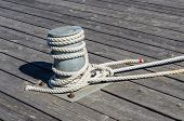stock photo of bollard  - Bollard with mooring rope on wooden quay in a harbor - JPG