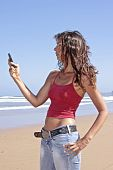 Beautiful young woman sending a text message on the beach