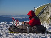 stock photo of thermos  - A man sits in a sleeping bag near the tent and snowshoes and drinking tea from a thermos on the background of the winter mountains - JPG