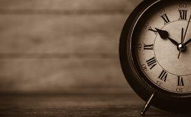 stock photo of analog clock  - Retro alarm clock on a table - JPG