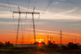 stock photo of electricity pylon  - Stunning landscape with wind generators power plant in background and high voltage electricity pylon in foreground at beautiful colorful sunrise - JPG
