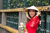 stock photo of traditional dress  - Portrait of attractive young lady in traditional Vietnamese dress and conical hat - JPG