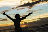foto of open arms  - strong confidence woman open arms under the sunrise at seaside - JPG