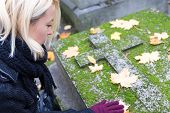 pic of headstones  - Solitary woman mourning with her hand on headstone - JPG