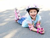 picture of roller-skating  - Happy little girl in pink roller skates and protective gear outdoor - JPG