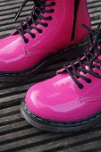 stock photo of skinhead  - Nice pink punk alternative girl or woman Military skinhead boots - JPG