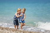 picture of brother sister  - Little brother and sister walking on the beach - JPG