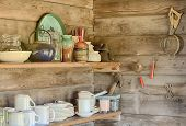 stock photo of log cabin  - A still life image of kitchecn shelves in an old log cabin showing the plates cups bowls and other houswares arranged on each shelf - JPG