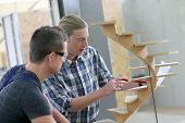 stock photo of carpentry  - Apprentice with adult in carpentry school working on wood - JPG