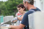 stock photo of mason  - Mason with trainee in construction - JPG