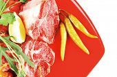 stock photo of red meat  - fresh raw beef red meat fillet medallion chunks on red plate isolated over white background - JPG