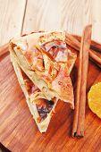 pic of cinnamon sticks  - sweet apple cake on wooden table with lemon and cinnamon sticks - JPG