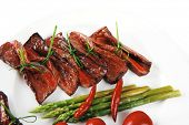 foto of white asparagus  - grilled red beef meat rolls with asparagus and hot spices on china plate isolated over white background - JPG