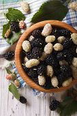 foto of mulberry  - Delicious fresh mulberry in a wooden bowl on the table - JPG
