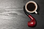 stock photo of tobacco-pipe  - Cup of coffee and a tobacco pipe on a wooden table - JPG