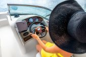 stock photo of top-hat  - Young and pretty woman in yellow skirt and swimsuit with hat and sunglasses driving luxury yacht in the sea - JPG
