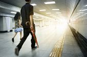 image of commutator  - Motion blurred commuters walking in subway station - JPG