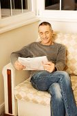 stock photo of only mature adults  - Mature man relaxing with newspaper on the sofa - JPG