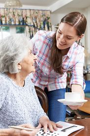 stock photo of grandmother  - Teenage Grandmother Bringing Grandmother Hot Drink At Table - JPG