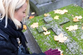stock photo of headstones  - Solitary woman mourning with her hand on headstone - JPG