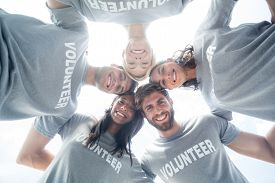 foto of huddle  - Low angle portrait of happy volunteers forming huddle - JPG