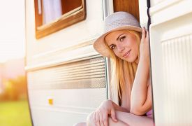 stock photo of camper  - Beautiful young woman sitting in a camper van on a summer day - JPG