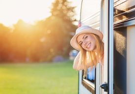 picture of camper  - Beautiful young woman sitting in a camper van on a summer day - JPG