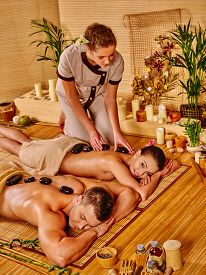 foto of stone-therapy  - Woman and man getting stone therapy massage in bamboo spa - JPG