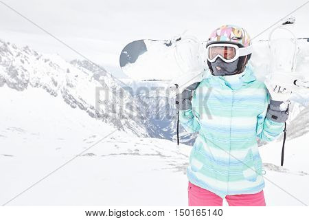 Female snowboarder wearing colorful helmet, blue jacket, grey gloves and pink pants standing standin