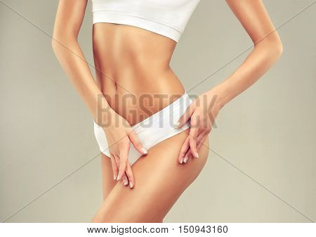 poster of Perfect slim toned young body of the girl . An example of sports , fitness or plastic surgery and aesthetic cosmetology.  Model woman shows the hip  and thigh  without cellulite