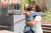 Cheerful best friends embracing each other outside coffee shop. Two young multiethnic guys hugging e poster