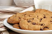 Freshly baked chocolate chip cookies with glass of milk.  Ceramic cookie jars in soft focus in the background.  Close-up with shallow dof.